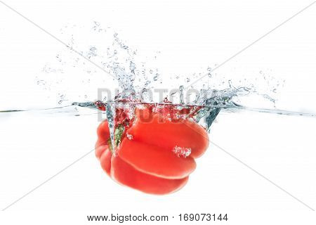 Red bellpepper dropped into the water with water splash on a white background