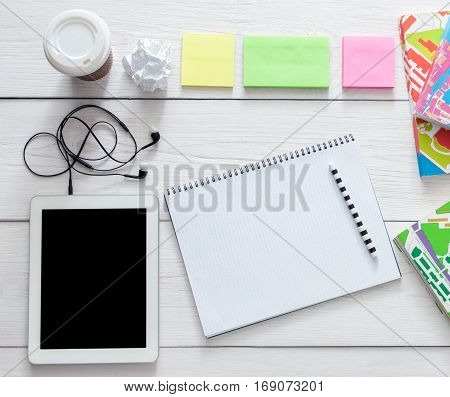 Student table background. Modern white office desk with tablet, smartphone and other supplies with coffee take away cup. Blank notebook page with copy space for text. Top view, flat lay.
