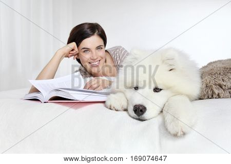 smiling woman with pet dog and book lying in bed