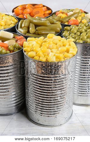 Closeup of a group of canned vegetables. Seven cans of mixed veggies, corn, peas, carrots and green beans.