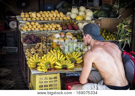Back view of young shirtless man choosing the fruits at the stand.