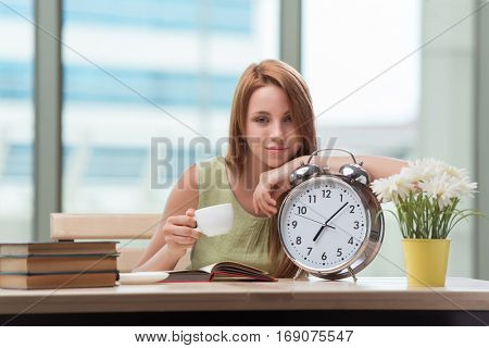 Student with gian alarm clock preparing for exams