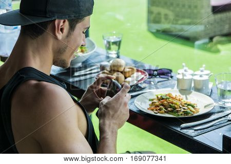 Side view of a man taking a shot of his food in the restaurant. Horizontal indoors shot.