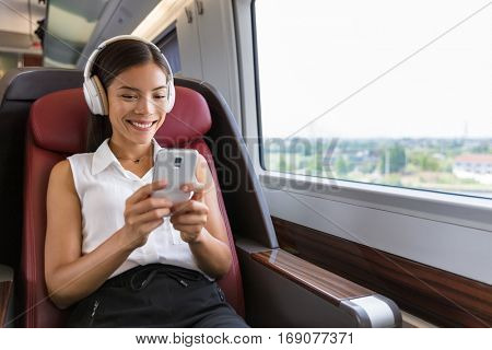 Modern people city lifestyle. Young urban woman using phone app and wireless headphones to listen to music or play video games online. Asian girl enjoying train travel in business class seat.
