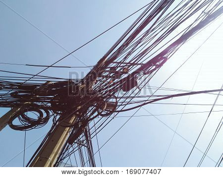 messy cable wire on electric pole against clear blue sky