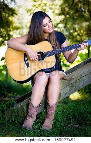 Beautiful girl playing guitar outside