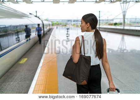 Tourist business woman leaving for trip on train with bag and luggage. Lady going on travel entering public transport.