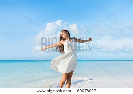 Freedom young woman carefree and happy with open arms on blue ocean landscape beach background. Asian girl in white dress feeling happiness enjoying her travel vacation.