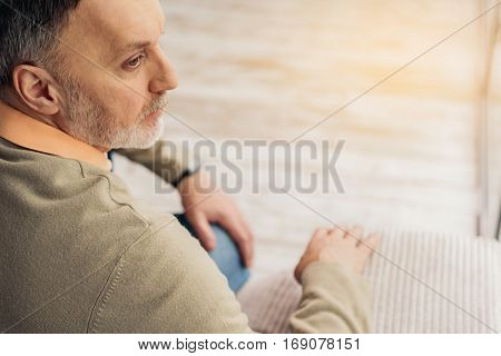 Serious male pensioner is thinking about something seriously. He is sitting on couch and looking aside with concentration