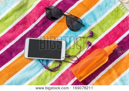 Travel essentials for beach summer vacation. Suntan accessories. What to bring on a holiday trip to the Caribbean: Music phone app and earphones, smartphone, sunglasses, sunscreen.