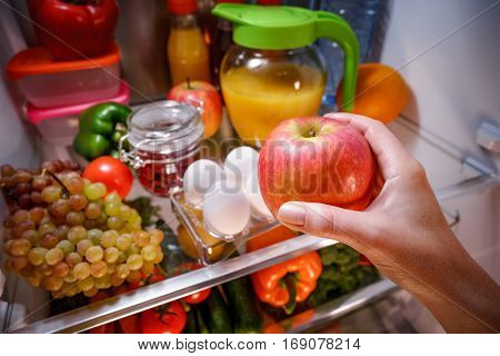 Woman takes the apple from the open refrigerator. Healthy food.