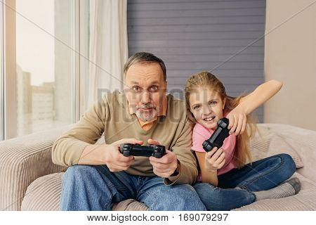 Cheerful granddaughter is having fun at home with her grandparent. They are holding joysticks and smiling. Family is looking forward with aspiration