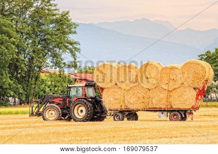 Tractor with cart loaded of hay bales.