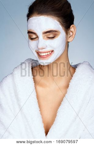 Laughing girl with moisturizing facial mask. Happy young woman smiling while wearing a face mask. Beauty & Skin care concept