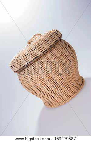 Round wicker basket with cover, isolated on white
