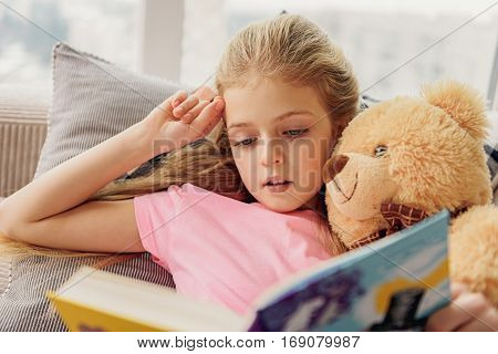 Pretty girl is reading book with interest. She is lying on couch and hugging her teddy bear