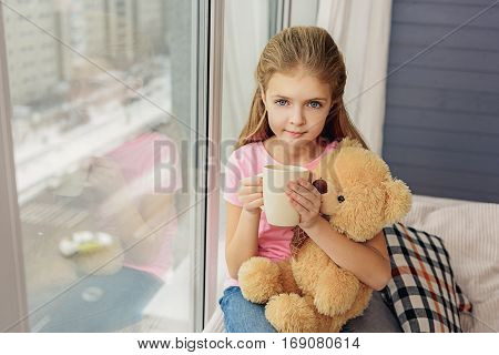 Innocent girl is drinking hot tea at home. She is sitting near window and holding teddy bear with pretty smile