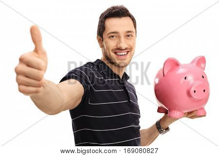 Happy man giving a thumb up and holding a piggybank isolated on white background