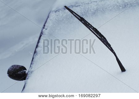 close up of a black raised car windscreen wiper covered in snow in winter time on a city street