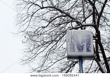 horizontal front view of metro sign covered in snow with trees in the background