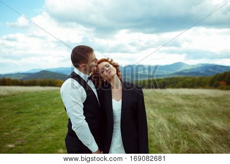 Bride Daydreams Being Dressed In Groom's Jacket Standing On The Field Among The Mountains