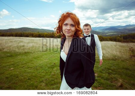 Bride Goes Forward Through The Field While Groom Follows Her