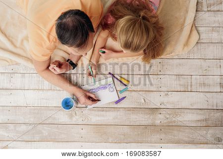 Top view of cheerful mature man and his granddaughter drawing picture by felt-tip pens together. They are lying on floor