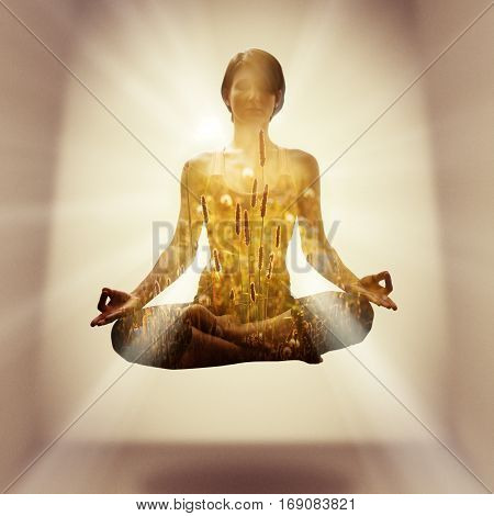 Yoga concept. The image is created using the multiple exposures. Image of a silhouette of a young woman soaring in the lotus position in the rays and meadow grass at sunrise