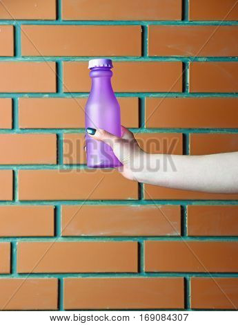 glass or plastic bottle violet color for juice or yoghurt drink as refreshment in female hand on textured brick wall background copy space