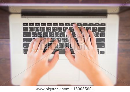 Typing on keyboard laptop top view of wooden table stock photo