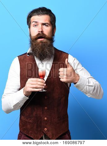 handsome bearded man with long beard and mustache on funny face tasting glass of alcoholic shot in vintage suede leather waistcoat on blue studio background