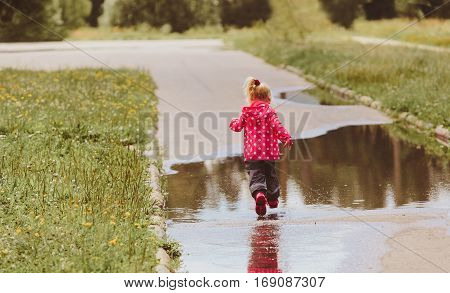 child run play in water puddle, kids seasonal activities