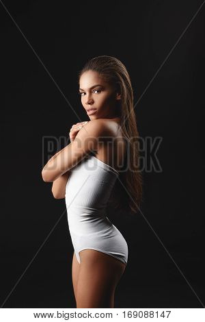 Sexy young afican woman is tight underwear is posing. She is standing and looking at camera with passion. Isolated on black background