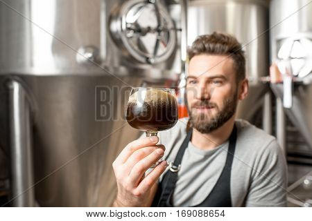 Handsome brewer in uniform checking quality of the beer sitting in the manufacturing with metal containers on the background