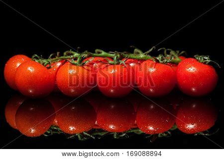 Red small tomatoes with water drops isolated on a blackbackground