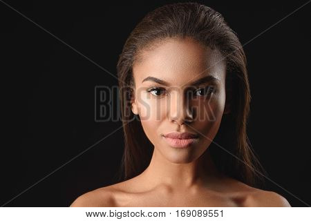 Portrait of attractive mulatto girl with perfect skin. She is looking at camera with confidence. Isolated and copy space in left side