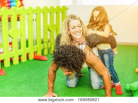 Happy multi ethnic family playing and laughing at playground kids center - Motherfather and daughter having fun in children playroom - Mixed race love concept - Focus on woman face - Warm filter