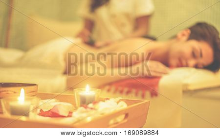 Young woman having hot stone therapy massage in spa resort hotel salon - Female enjoying relaxing back massage - Body care skin care wellness concept - Focus on right candle - Warm cinematic filter