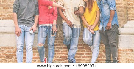 Multi ethnic friends watching videos on mobile phones in university break - Young friends addiction to new technology trends - Addicted people mania of new generations - Focus on center man hand
