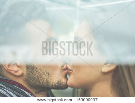 Young couple in love kissing under the rain with transparent umbrella - Handsome bearded man and woman enjoying havig tender moments - Dating concept - Focus on their mouths - Warm cinematic filter