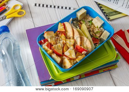 Healthy school lunch for child or teenager. Pile of exercise books, water and food in lunch box on white wood table, cracker with cheese and apples
