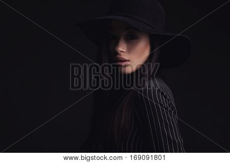 Beautiful woman wearing retro hat and black striped shirt. fashion studio shoot.