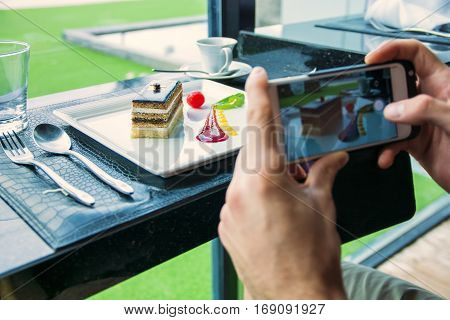 Side view of a man taking a photo of his food in the restaurant. Horizontal indoors shot.