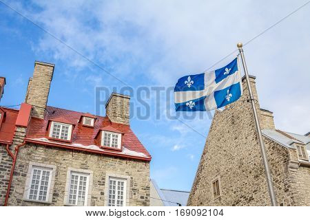 Quebec flag in front of historic houses of the Old Quebec city