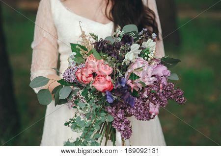 Beautiful bride in the forest with a large bouquet of different flowers. Rustic style
