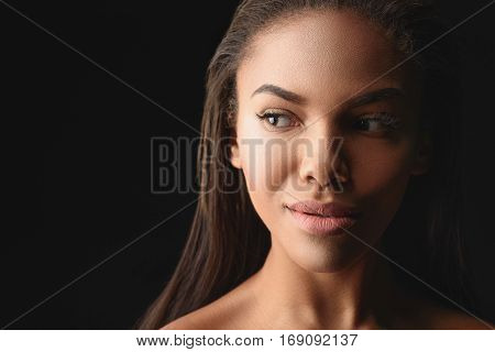 Seductive young mulatto woman is looking aside with curiosity and flirting. Isolated and copy space in left side