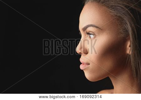 Close up of beautiful mulatto girl face in profile. She is looking forward with passion. Isolated on black background. Copy space in left side