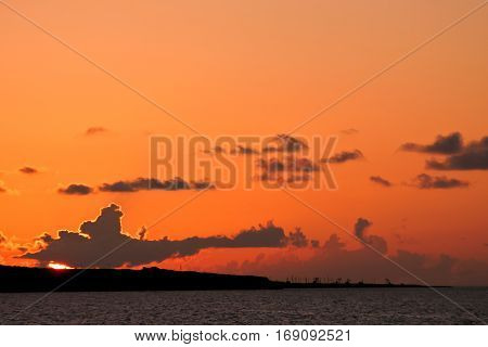 Sunset on a background of silhouettes of the industrial landscape. Majestic and dramatic scene of nature.