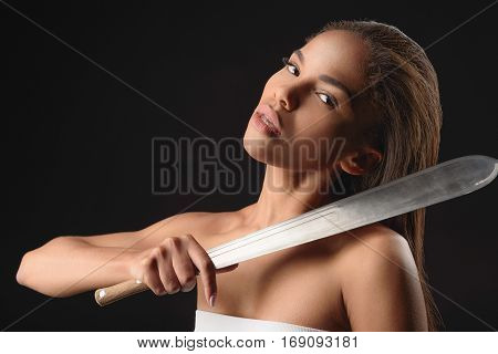 Irritated african girl is threatening to someone. She is standing and holding machete near neck. Isolated