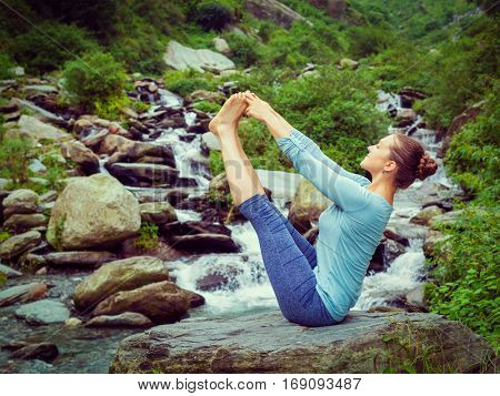 Yoga outdoors -  woman doing Ashtanga Vinyasa Yoga balance asana Ubhaya padangusthasana Big Double Toe Yoga Pose at tropical waterfall in Himalayas in India. Vintage retro effect hipster style image.